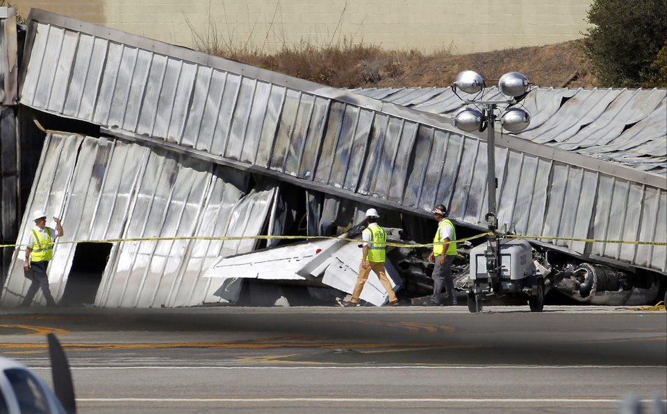 Photo - FILE - In this Sept. 30, 2013, file photo National Transportation Safety Board (NTSB) investigators walk by the tail of the private jet, which crashed into a hangar at the Santa Monica Municipal Airport in California, as they await the arrival of a crane to access the plane. As a result of the Oct. 1 federal government partial shutdown almost all of the board's 400 employees were furloughed, an NTSB spokeswoman said. Across America the government's work is piling up, and it's not just paperwork. (AP Photo/Nick Ut, File)