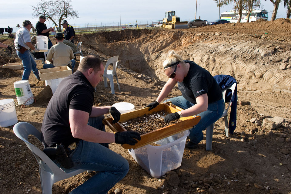 Photo -   San Joaquin Sheriff detectives Paul Hoskins, left, and Lindsay Smith sift for human remains that were excavated from an abandoned cattle ranch near Linden, Calif., Sunday, Feb. 12, 2012. Sacramento television station KCRA reports human bones found Sunday were recovered along with two pairs of shoes, sandals, tennis shoes, engraved jewelry and a woman's purse. (AP Photo/The Record, Craig Sanders)