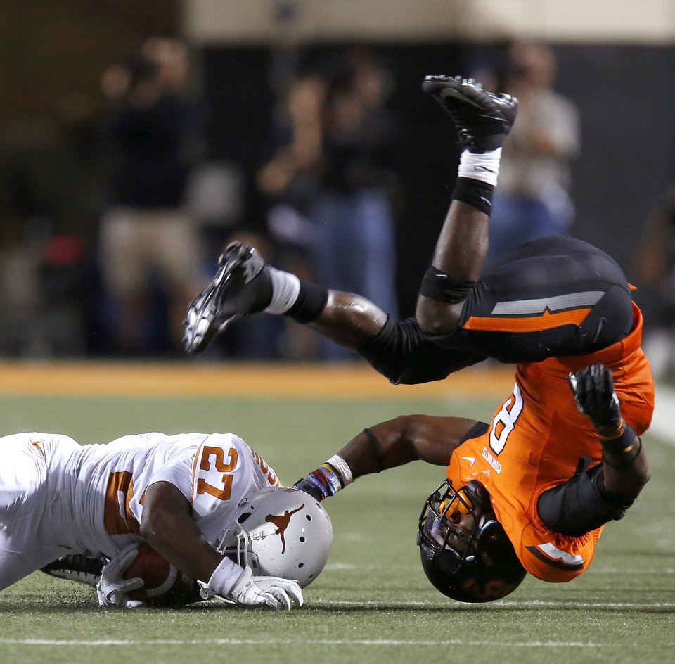 Photo - Oklahoma State's Daytawion Lowe (8) flips over after trying to bring down Texas' Daje Johnson (27) during a college football game between Oklahoma State University (OSU) and the University of Texas (UT) at Boone Pickens Stadium in Stillwater, Okla., Saturday, Sept. 29, 2012. Oklahoma State lost 41-36. Photo by Bryan Terry, The Oklahoman
