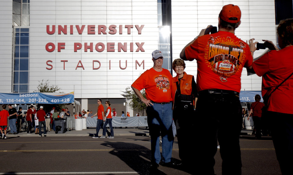 Photo - Sharon and Roger Sample, of Stillwater, Okla., get their picture taken in front of the stadium before the Fiesta Bowl between the Oklahoma State University Cowboys (OSU) and the Stanford Cardinal at the University of Phoenix Stadium in Glendale, Ariz., Monday, Jan. 2, 2012. Photo by Bryan Terry, The Oklahoman