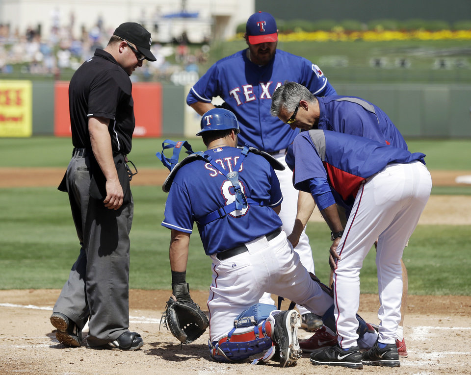 Photo - Texas Rangers catcher Geovany Soto, second from left, is examined by trainers and coaches during the second inning of a spring exhibition baseball game against the San Diego Padres, Sunday, March 23, 2014, in Surprise, Ariz. Soto was taken out of the game. (AP Photo/Darron Cummings)