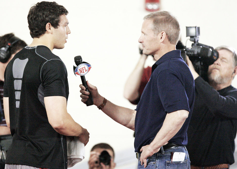 Photo - Sam Bradford, left, talks with the NFL Network's Mike Mayock after his NFL Pro Day workout at the Everest Training Center in Norman on Monday.  Photo by Steve Gooch, The Oklahoman