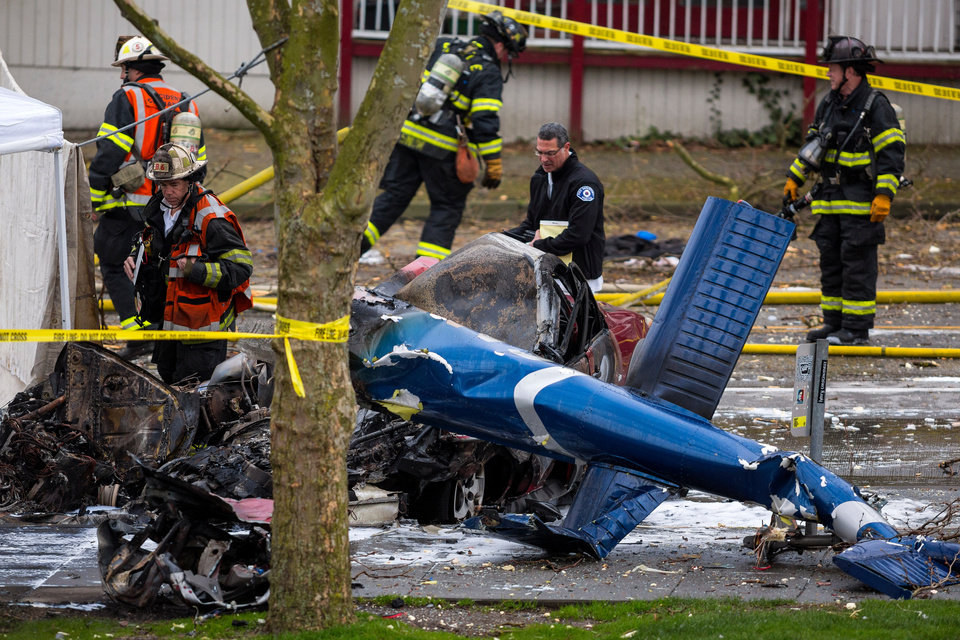 Photo - Investigators and emergency personnel look over the aftermath of a news helicopter crash Tuesday, March 18, 2014, in Seattle, Wash. A KOMO-TV helicopter crashed into a city street near Seattle's Space Needle, killing two people and critically injuring a person in a car on the ground. (AP Photo/seattlepi.com, Jordan Stead) MAGS OUT; NO SALES; SEATTLE TIMES OUT; MANDATORY CREDIT; TV OUT