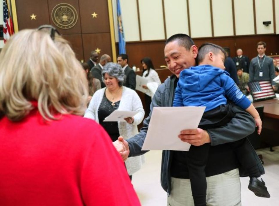 Photo -  Willy Vue, France, and his son, Dominik, 3, at the naturalization ceremony at the District Court for the Western District of Oklahoma, Friday, February 28, 2020.  [Photo by Doug Hoke/The Oklahoman]
