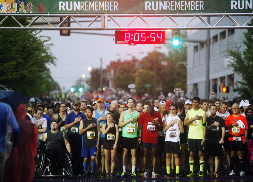 Photo - Runners at the starting line pay tribute to the national anthem before the start of the 14th Annual Oklahoma City Memorial Marathon in Oklahoma City, Sunday, April 27, 2014. The marathon was delayed over two hours beyond it's original start time of 6 a.m. Photo by KT King/The Oklahoman