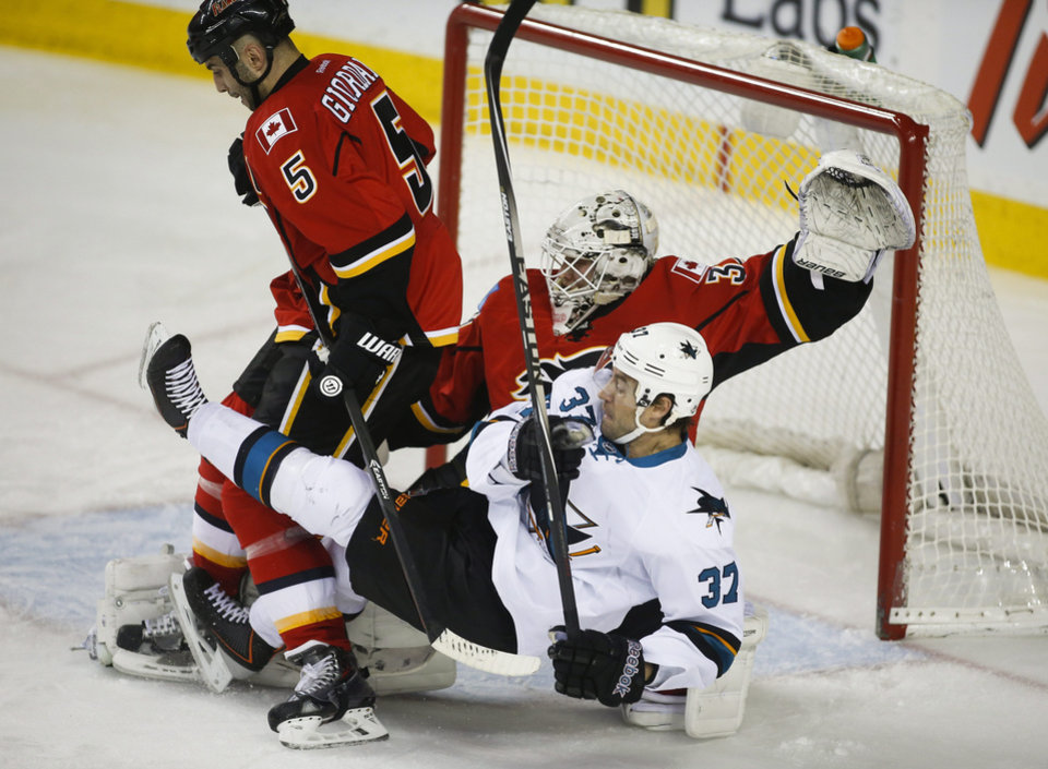 Photo - San Jose Sharks' Adam Burish, right, gets knocked to the ice by Calgary Flames' Mark Giordano, left, as goalie Karri Ramo, from Finland, guards the net during second period NHL hockey action in Calgary, Monday, March 24, 2014. (AP Photo/The Canadian Press, Jeff McIntosh)