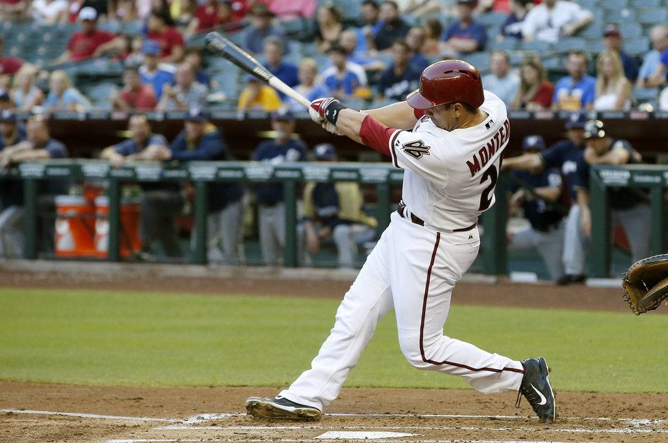 Photo - Arizona Diamondbacks' Miguel Montero connects for an RBI single against the Milwaukee Brewers during the first inning of a baseball game on Tuesday, June 17, 2014, in Phoenix. (AP Photo/Ross D. Franklin)