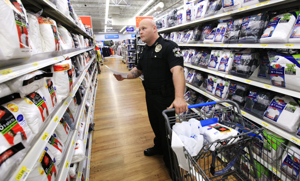 Photo - Oklahoma County deputy sheriff James Palmer shops for Christmas presents for a 16 year-old boy at a local Wal-Mart store as local law enforcement, in partnership with Sunbeam Family Services, select gifts for the Grandparents Raising Grandchildren Program.  PAUL B. SOUTHERLAND - PAUL B. SOUTHERLAND