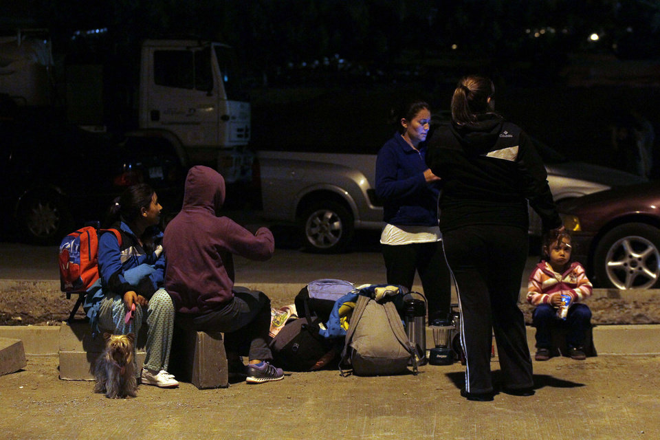 Photo - People sit outside their homes after a strong aftershock in Arica, Chile, early Thursday, April 3, 2014. A powerful 7.8-magnitude aftershock hit Chile's far-northern coast late Wednesday night, shaking the same area where a magnitude-8.2 earthquake hit just a day before causing some damage and six deaths. (AP Photo/Luis Hidalgo)