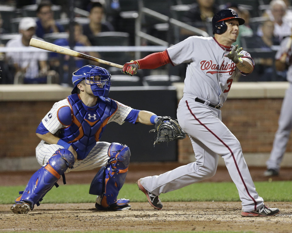 Photo - New York Mets catcher Travis d'Arnaud, left, watches a ball hit by Washington Nationals' Asdrubal Cabrera, for a home run during the eighth inning a baseball game Wednesday, Aug. 13, 2014, in New York.  (AP Photo/Frank Franklin II)