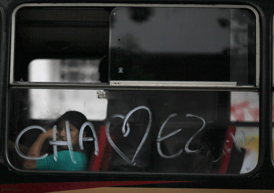 Photo -   A woman looks out a bus window spray painted with the last name of Venezuela's President Hugo Chavez, in Caracas, Venezuela, Friday, Oct. 5, 2012. Venezuelans head to the polls Sunday to vote in their country's presidential election, deciding between Chavez and opposition candidate Henrique Capriles. (AP Photo/Ariana Cubillos)