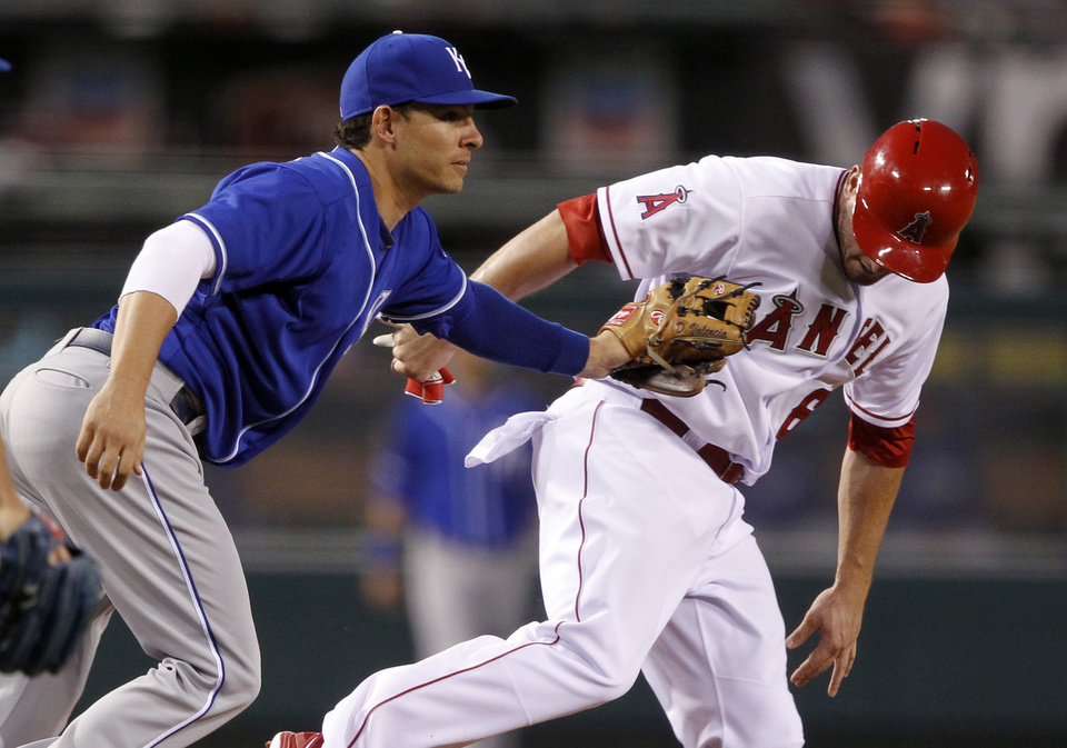 Photo - Kansas City Royals third baseman Danny Valencia, left, tags out Los Angeles Angels' David Freese in a rundown between third and second base, on a fielder's choice to the pitcher by Angel's Erick Aybar, in the 10th inning of a baseball game Saturday, May 24, 2014, in Anaheim, Calif. (AP Photo/Alex Gallardo)