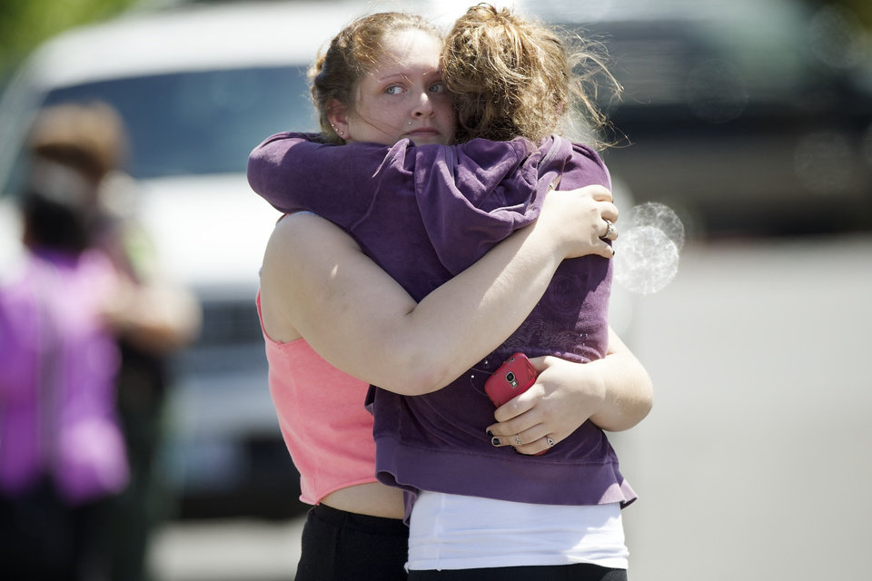 Photo - Briannah Wilson, 21, left, and her sister Brittanie Wilson, 19, right, embrace after students arrived at shopping center parking lot in Wood Village, Ore., after a shooting at Reynolds High School Tuesday, June 10, 2014, in nearby Troutdale. A gunman killed a student at the high school east of Portland Tuesday and the shooter is also dead, police said. (AP Photo/Troy Wayrynen)