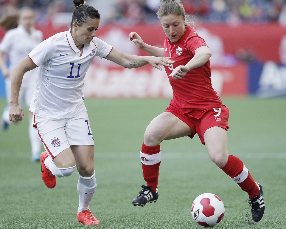 Photo - United States defender Ali Krieger (11) defends against Canada forward Josee Belanger (9) during first half of an exhibition soccer match in Winnipeg, Manitoba, Thursday, May 8, 2014. (AP Photo/The Canadian Press, John Woods)