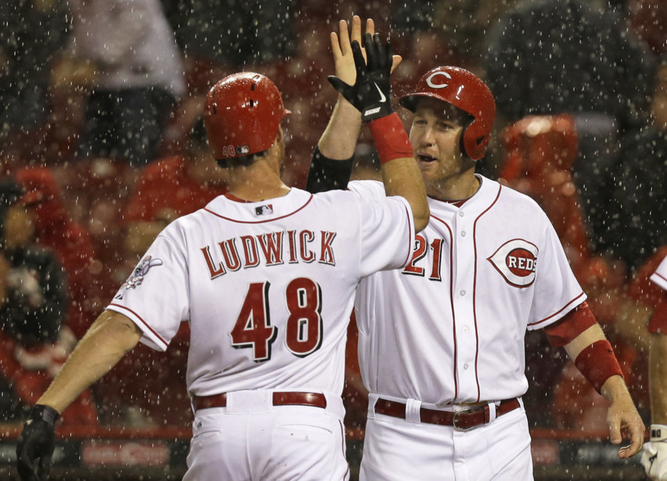 Photo - Cincinnati Reds' Ryan Ludwick (48) is congratulated by Todd Frazier (21) after Ludwick hit a two-run home run off Pittsburgh Pirates starting pitcher Wandy Rodriguez in the fourth inning of a baseball game being played in the rain, Monday, April 14, 2014, in Cincinnati. (AP Photo/Al Behrman)