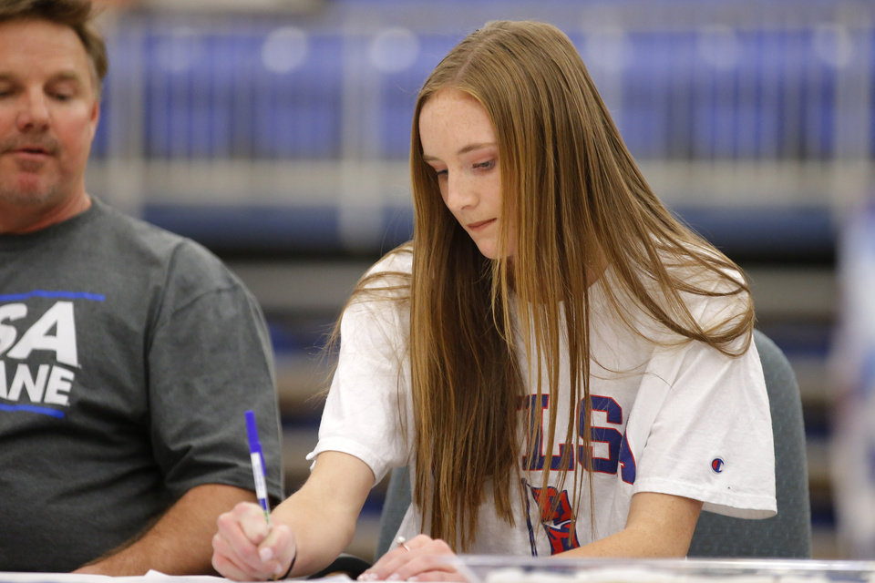 Photo - Deer Creek soccer player Grayson Schimmels signs a letter of intent to play soccer at University of Tulsa as her father Donnie Schimmels watches during a signing day ceremony at Deer Creek High School, Wednesday, Feb. 7, 2018.  Photo by Bryan Terry, The Oklahoman