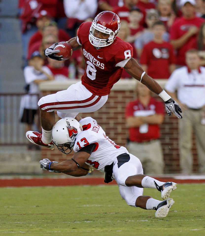 Photo - Oklahoma's Dominique Whaley (8) leaps over Ball State's Armand Dehaney (13) during the college football game between the University of Oklahoma Sooners (OU) and the Ball State Cardinals at Gaylord Family-Memorial Stadium on Saturday, Oct. 01, 2011, in Norman, Okla. Photo by Bryan Terry, The Oklahoman