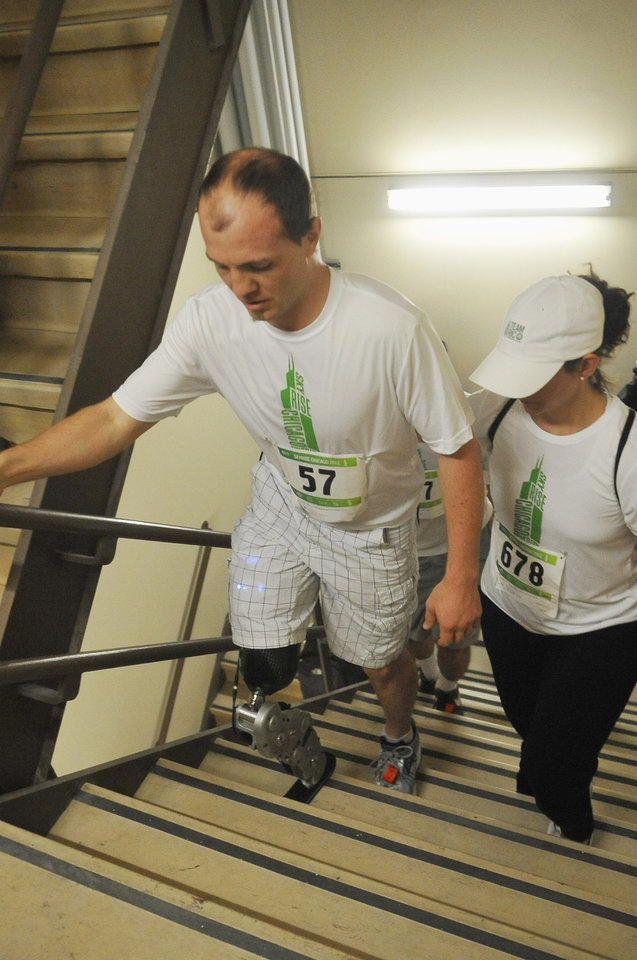 "Zac Vawter, left, a 31-year-old amputee, walks up the stairs of the Willis Tower in Chicago, Sunday, Nov. 4, 2012, to become the first person to climb the 103 floors of one of the world's tallest skyscrapers with a bionic leg. Vawter was wearing a prosthetic leg controlled by his mind when he participated in ""SkyRise Chicago."" (AP Photo/Chicago Sun-Times, Brian Jackson) CHICAGO LOCALS OUT, MAGS OUT"