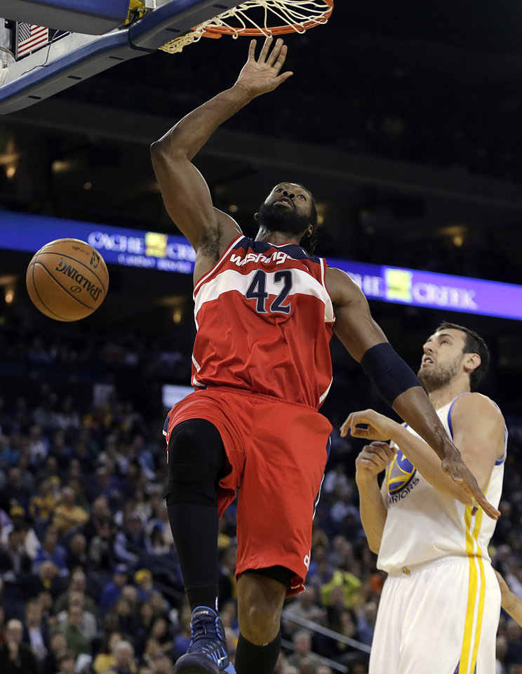 Photo - Washington Wizards' Nene Hilario (42) scores over Golden State Warriors' Andrew Bogut, right, during the first half of an NBA basketball game, Tuesday, Jan. 28, 2014, in Oakland, Calif. (AP Photo/Ben Margot)