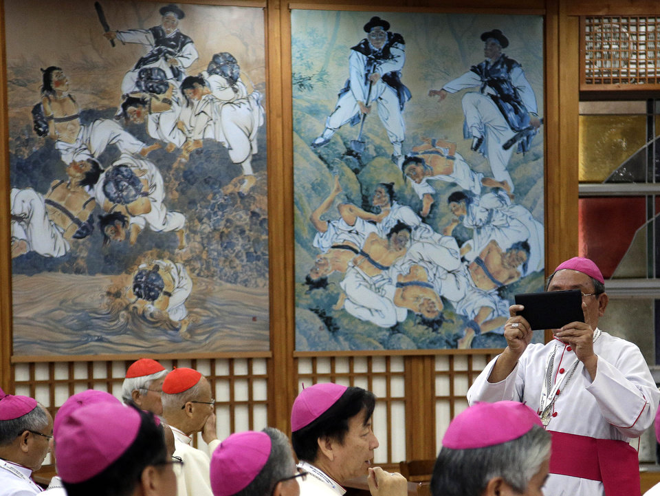 Photo - A Bishop takes pictures as he waits to meet with Pope Francis at the Shrine of Haemi, in South Korea, Sunday, Aug. 17, 2014. (AP Photo/Gregorio Borgia)