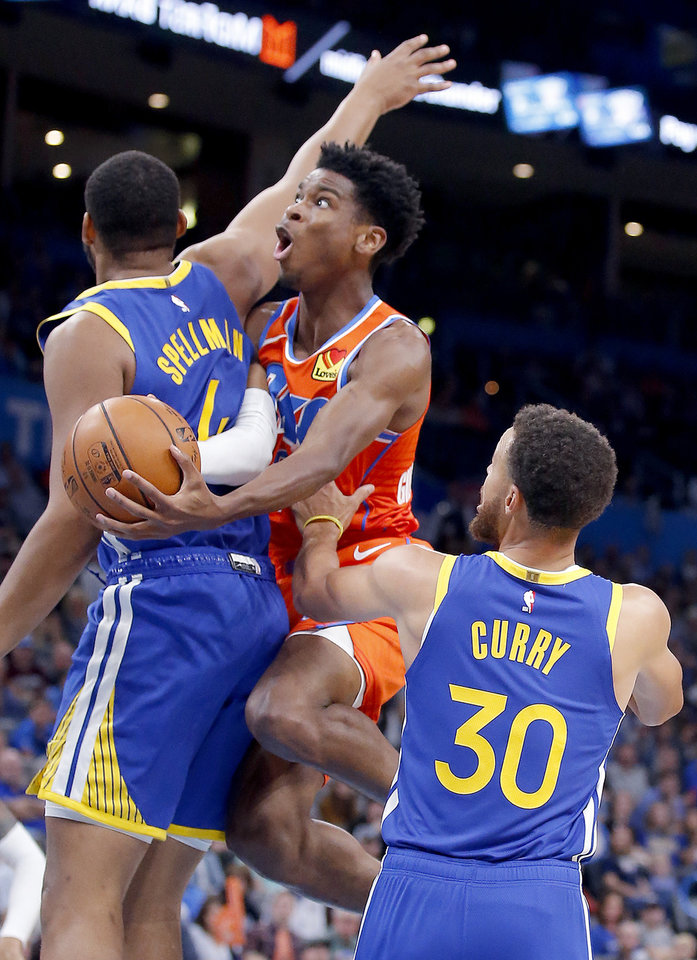 Photo - Oklahoma City's Shai Gilgeous-Alexander (2) goes to the basket in between Golden State's Omari Spellman (4) and Stephen Curry (30) during the NBA game between the Oklahoma City Thunder and Golden State Warriors at Chesapeake Energy Arena,  Sunday, Oct. 27, 2019. Thunder won 120-92.[Sarah Phipps/The Oklahoman]