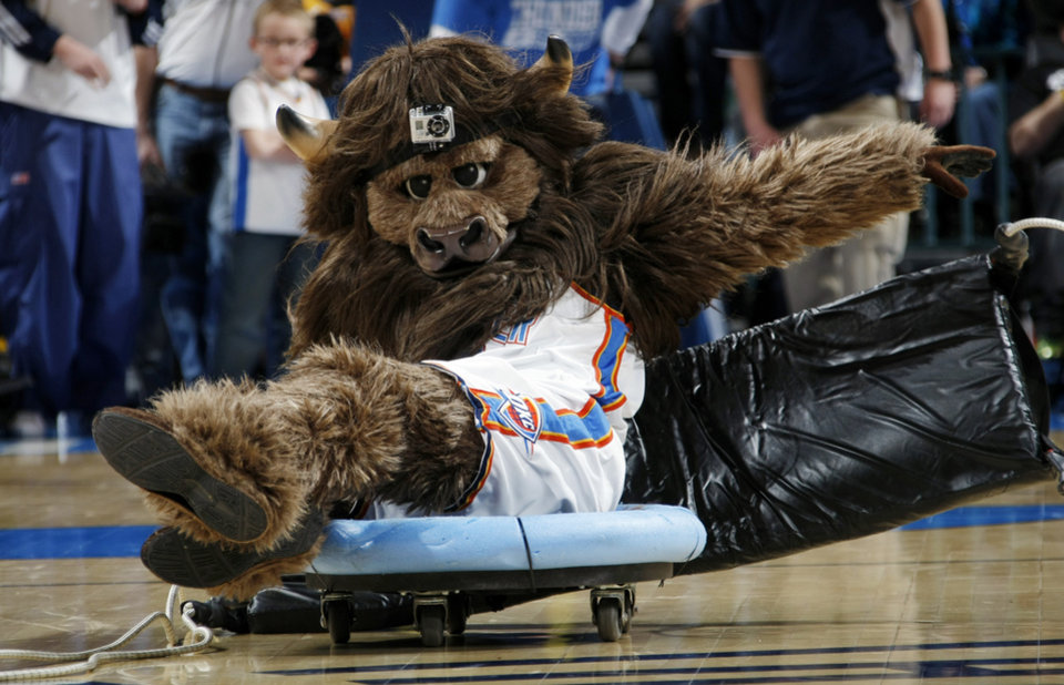Photo - Oklahoma City mascot Rumble the Bison slides across the court as part of a game of Bison Bowling during a break in the action at the NBA basketball game between the Washington Wizards and the Oklahoma City Thunder at the Oklahoma City Arena in Oklahoma City, Friday, January 28, 2011. Photo by Nate Billings, The Oklahoman