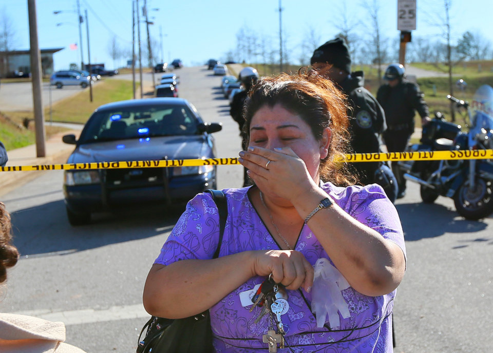 Photo - A distraught woman is turned back by police at the scene of a school shooting at Price Middle school in Atlanta on Thursday, Jan. 31, 2013. A 14-year-old boy was wounded outside the school Thursday afternoon and a fellow student was in custody as a suspect, authorities said. No other students were hurt. (AP Photo/Atlanta Journal-Constitution, Curtis Compton) MARIETTA DAILY OUT; GWINNETT DAILY POST OUT; LOCAL TV OUT; WXIA-TV OUT; WGCL-TV OUT