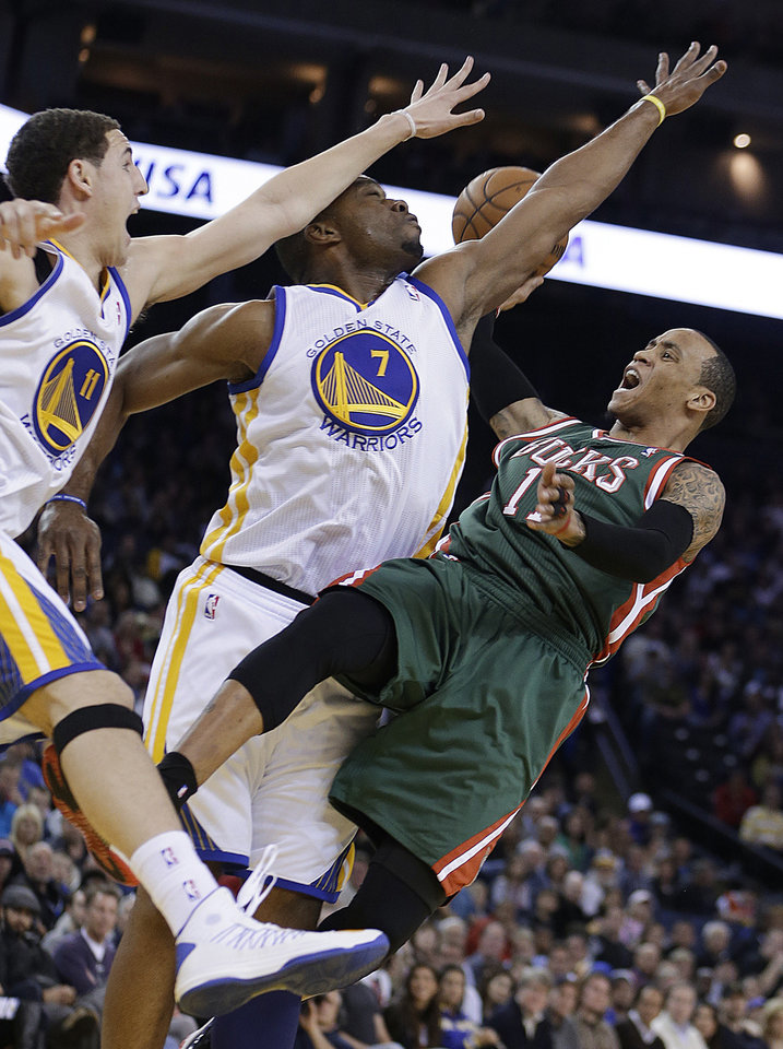 Milwaukee Bucks' Monta Ellis, right, has his shot blocked by Golden State Warriors' Carl Landry (7) and Klay Thompson (11) during the first half of an NBA basketball game Saturday, March 9, 2013, in Oakland, Calif. (AP Photo/Ben Margot)