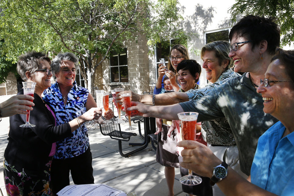 Photo - Longtime same-sex couple Angie Holley, far left, and Bylo Farmer share a toast with friends celebrating with their new marriage license, in front of the offices of the Boulder County Clerk and Recorder, in Boulder, Colo., Thursday, June 26, 2014. Together eight years, Holley and Farmer decided to become officially married after Boulder County Clerk Hillary Hall began issuing licenses a day earlier following a federal appeals court ruling that Utah's same-sex marriage ban is unconstitutional. More couples showed up in Boulder on Thursday to get licenses. (AP Photo/Brennan Linsley)
