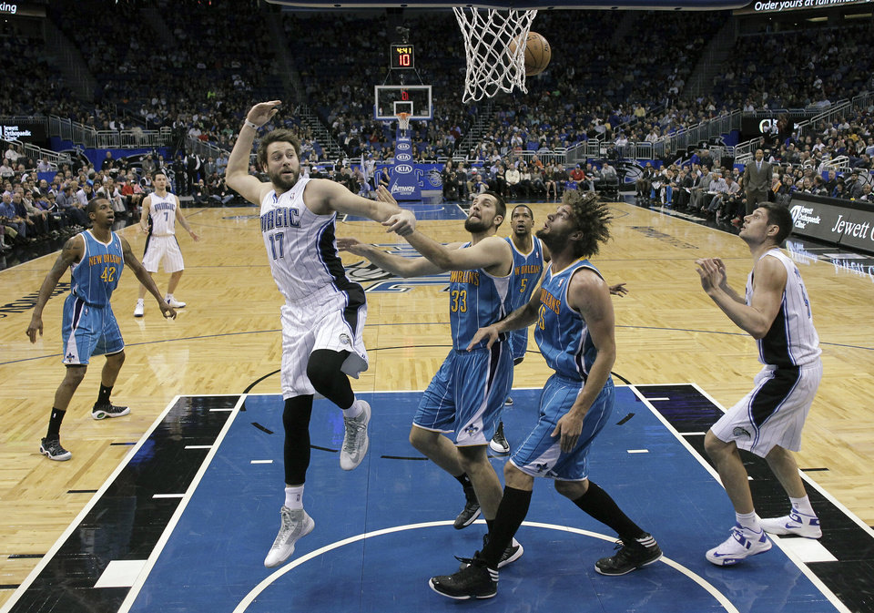 Orlando Magic's Josh McRoberts (17) passes the ball behind his head to Nikola Vucevic, right, of Montenegro, as he is defended by New Orleans Hornets' Ryan Anderson (33), Dominic McGuire (5) and Robin Lopez (15) during the first half of an NBA basketball game on Wednesday, Dec. 26, 2012, in Orlando, Fla. (AP Photo/John Raoux)