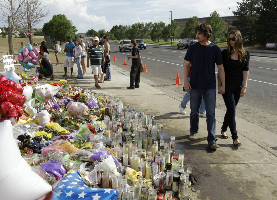 Actor Christian Bale, second right, and his wife Sibi Blazic, right, visit a memorial to the victims of Friday\'s mass shooting, Tuesday, July 24, 2012, in Aurora, Colo. Twelve people were killed when a gunman opened fire during a late-night showing of the movie Dark Knight Rises, which stars Bale as Batman. (AP Photo/Ted S. Warren)