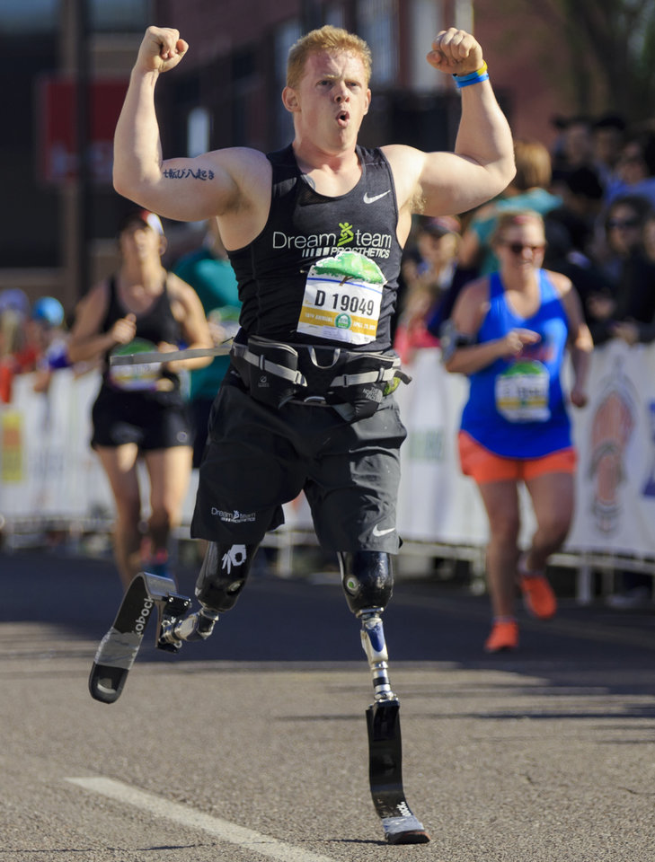 Photo - Trevor Bunch reacts as he finishes the half marathon during the Oklahoma City Marathon in Oklahoma City, Okla. on Sunday, April 29, 2018.  . Photo by Chris Landsberger, The Oklahoman