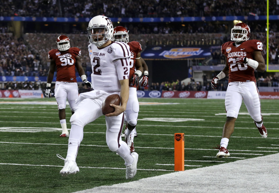 ADVANCE FOR WEEKEND EDITIONS, AUG. 10-11 - FILE - In this Jan. 4, 2013, file photo, Texas A&M\'s Johnny Manziel (2) steps into the end zone for a touchdown as Oklahoma\'s Frank Shannon (20) and others give chase during the first half of the Cotton Bowl NCAA college football game in Arlington, Texas. Points have never been more plentiful in college football. If touchdowns could be weighed they\'d be measured in tons. And yards? The days when a QB was a rare commodity if he could run and pass well are long gone. (AP Photo/LM Otero) ORG XMIT: NY157