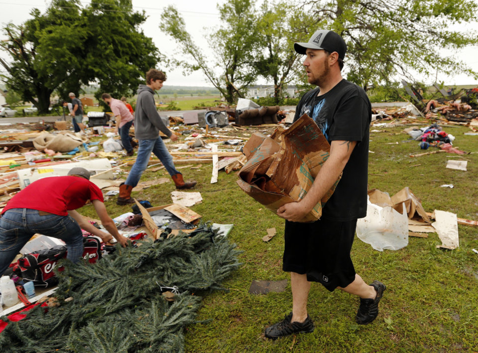 Photo - Kris Allen carries a box as friends and family look for mementos and valuables in the wreckage of his and wife Christeen's mobil home destroyed by storms on Friday, April 29, 2016 in Ninnekah, Okla.  Photo by Steve Sisney, The Oklahoman