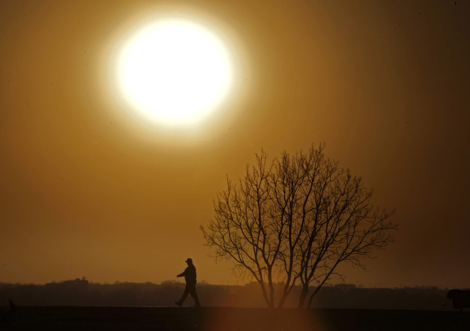 A person walks at Lake Hefner as dust from high winds fill the air in Oklahoma City, Sunday, Jan. 22, 2012. Photo by Sarah Phipps, The Oklahoman