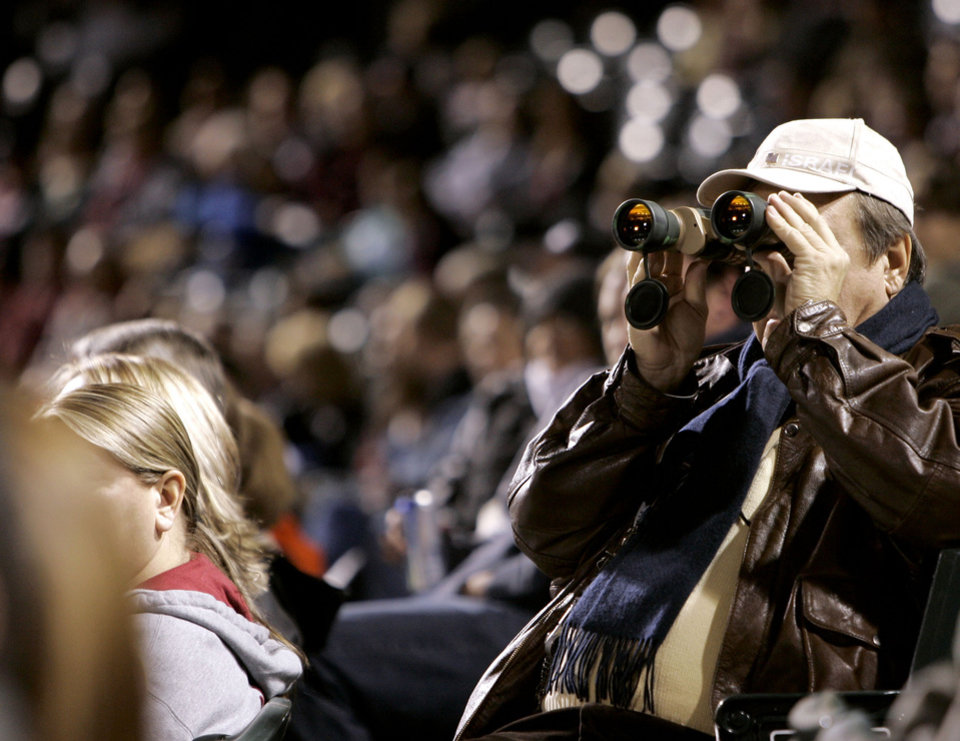 Photo - Bill Crozier, of Union City, uses his binoculars to get a good look at the Centennial Spectacular playing on the outfield monitor at the AT&T Bricktown Ballpark in Oklahoma City as part of the State's Centennial celebration. By John Clanton, The Oklahoman