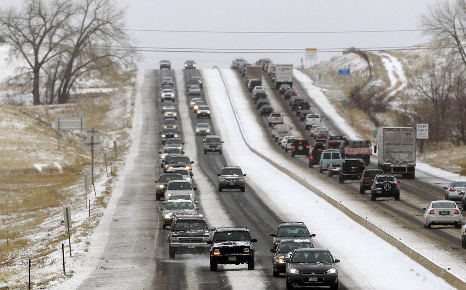Photo - Traffic winds its way east and west along a snowy Boulder-Denver Turnpike, in Superior, Colo., Wednesday Dec. 19, 2012. A storm that has dumped more than a foot of snow in the Rocky Mountains is heading east and is forecast to bring the first major winter storm of the season to the central plains and Midwest. (AP Photo/Brennan Linsley)