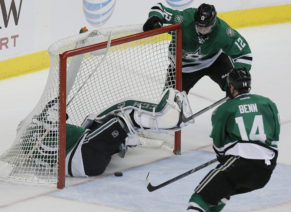 Photo - Dallas Stars goalie Kari Lehtonen (32) falls into the net as forwards Jamie Benn (14) and Alex Chiasson (12) rush to prevent the puck from crossing the goal line in the second period of an NHL hockey game against the Detroit Red Wings, Saturday, Jan. 4, 2014, in Dallas. The Red Wings did not score on the play. (AP Photo/Brandon Wade)