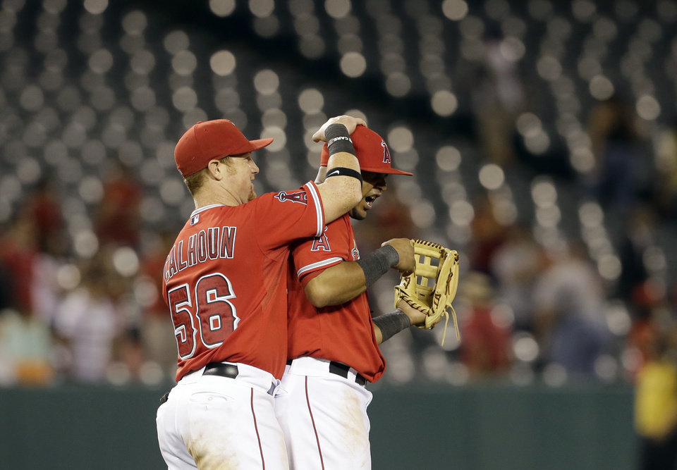 Photo - Los Angeles Angels Kole Calhoun, left, and Luis Jiminez celebrate their 11-2 win over the Tampa Bay Rays in a baseball game in Anaheim, Calif., Monday, Sept. 2, 2013. (AP Photo/Reed Saxon)