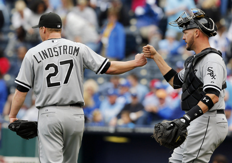 Photo - Chicago White Sox relief pitcher Matt Lindstrom (27) and catcher Tyler Flowers, right, fist bump following a baseball game against the Kansas City Royals at Kauffman Stadium in Kansas City, Mo., Sunday, April 6, 2014. The White Sox won 5-1. (AP Photo/Orlin Wagner)