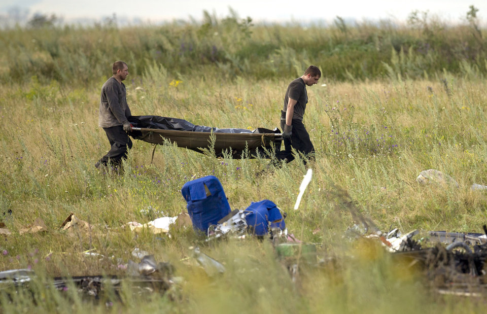 Photo - Emergency workers carry the body of a victim at the crash site of Malaysia Airlines Flight 17 near the village of Hrabove, eastern Ukraine, Saturday, July 19, 2014. World leaders demanded Friday that pro-Russia rebels who control the eastern Ukraine crash site of Malaysia Airlines Flight 17 give immediate, unfettered access to independent investigators to determine who shot down the plane. (AP Photo/Vadim Ghirda)