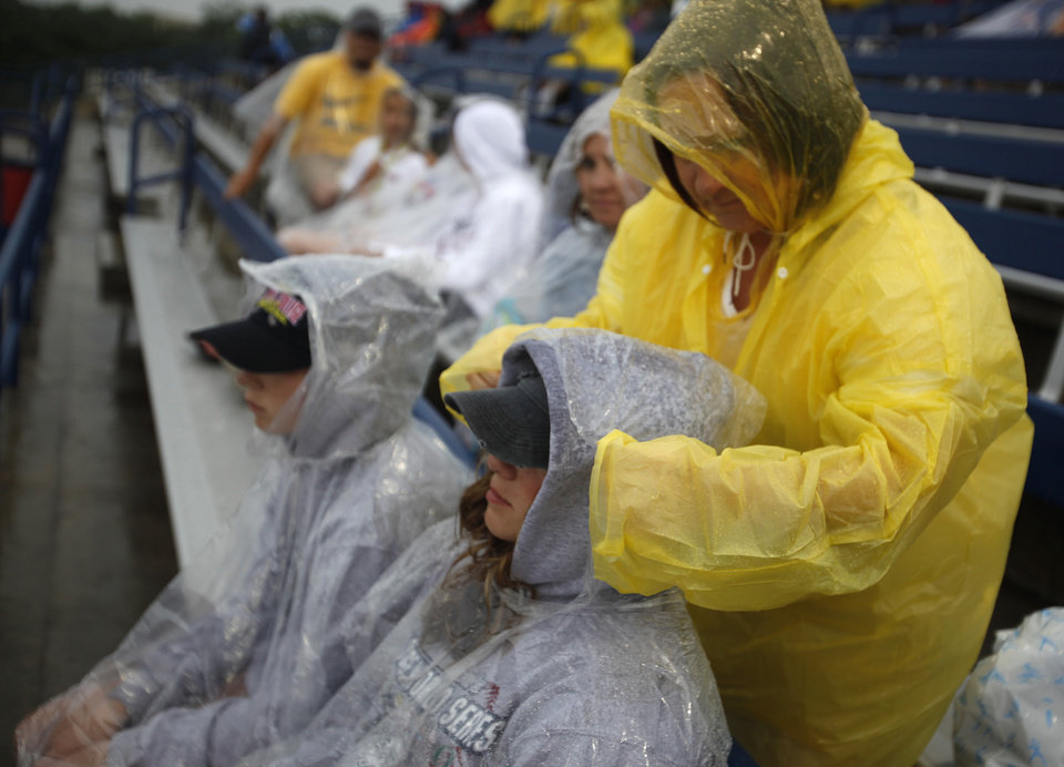 Lisa Haynes, of North Carolina, fixes Lindsey Haynes\' poncho at ASA Hall of Fame Stadium in Oklahoma City, Wednesday, June 6, 2012. The Women\'s College World Series softball championship game was delayed due to rain. Photo by Garett Fisbeck, The Oklahoman