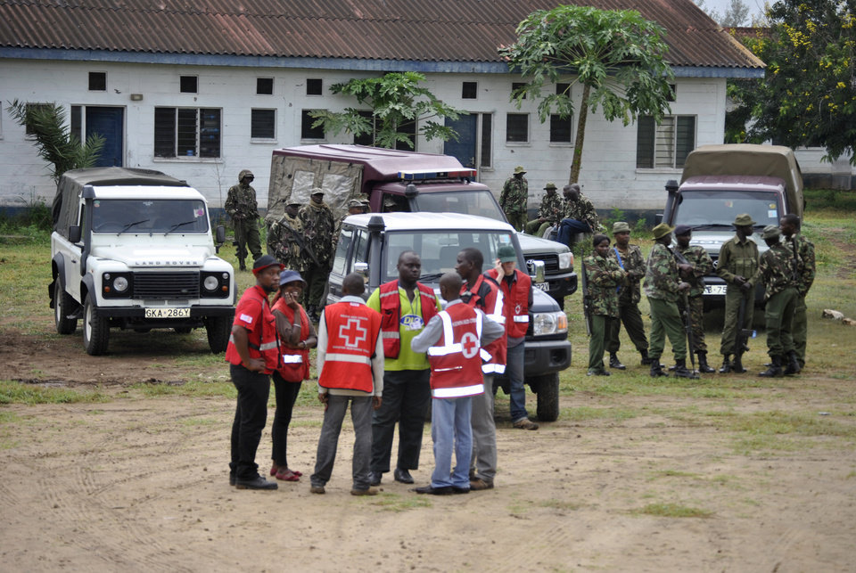 Photo - Security personnel and Kenya Red Cross officials stand at the site where gunmen attacked, in Gamba Kenya, Sunday, July 6, 2014. Eighteen people were killed in overnight attacks by the gunmen in two counties on the Kenyan coast, where last month al-Qaida-linked militants claimed responsibility for killing 65 people, the Kenya Red Cross said Sunday. The Sunday attacks took place in the towns of Hindi in Lamu county and Gamba in Tana River, the Kenya Red Cross chief Abbas Gulet said. Al-Qaida-linked al-Shabab militants from Somalia claimed responsibility for the attacks. (AP Photo)