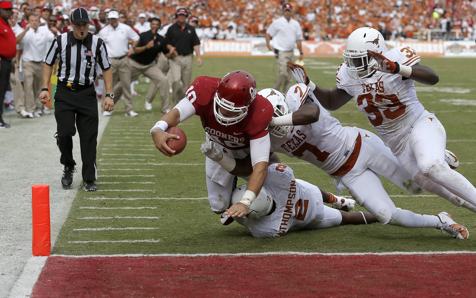 Photo - OU's Blake Bell (10) scores a touchdown beside UT's Mykkele Thompson (2), Demarco Cobbs (7), and Steve Edmond (33) during the Red River Rivalry college football game between the University of Oklahoma (OU) and the University of Texas (UT) at the Cotton Bowl in Dallas, Saturday, Oct. 13, 2012. Photo by Bryan Terry, The Oklahoman