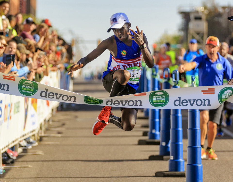 Photo -  Nathan Chamer jumps across the finish line Sunday as he wins the Oklahoma City Marathon's men's race. It was Chamer's first marathon. [Photo by Chris Landsberger, The Oklahoman]