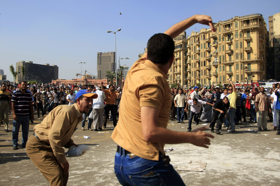 Photo -   A protester throws a stone after scuffles broke out between groups of several hundred protesters in Tahrir square when chants against the new Islamist president angered some in the crowd in Cairo, Egypt, Friday, Oct. 12, 2012. The scuffles between supporters and opponents of President Mohammed Morsi reflect deep political divisions among the country's 82 million people, more than a year after the popular uprising that toppled Hosni Mubarak. (AP Photo/Khalil Hamra)