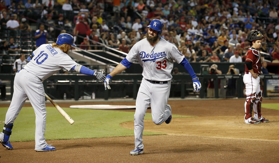 Photo - Los Angeles Dodgers' Scott Van Slyke (33) shakes hands with teammate Justin Turner (10) after Van Slyke's home run as Arizona Diamondbacks' Tuffy Gosewisch, right, looks on during the third inning of a baseball game Wednesday, Aug. 27, 2014, in Phoenix. (AP Photo/Ross D. Franklin)