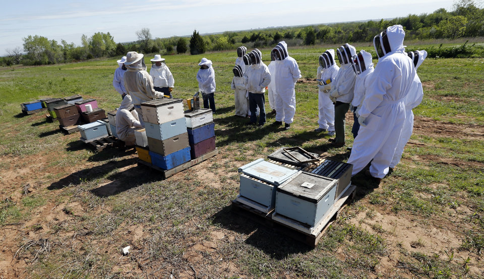Participants wear bee suits as Brian Royal demonstrates bee keeping techniques to the Noble Bee Keepers Club at his home based business on Saturday, May 4, 2013, in Norman, Okla.  