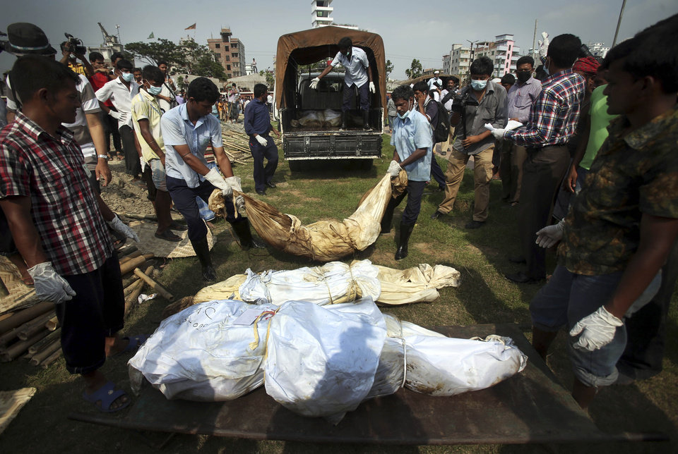 Workers unload unclaimed bodies from the building that collapsed last week in preparation for a mass burial on Wednesday, May 1, 2013, in Dhaka, Bangladesh. Several hundred people attended a mass funeral in a Dhaka suburb for 18 unidentified workers who died in the building housing garment factories that collapsed last week in the country's worst industrial disaster, killing at least 402 people and injuring 2,500.   (AP Photo/Wong Maye-E)