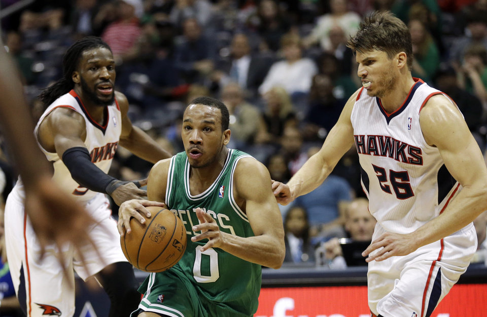 Photo - Boston Celtics' Avery Bradley, center, drives to the hoop against Atlanta Hawks' DeMarre Carroll, left, and Kyle Korver, right, in the fourth quarter of an NBA basketball game, Wednesday, April 9, 2014, in Atlanta. The Hawks won 105-97. (AP Photo/David Goldman)